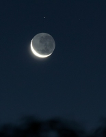 Crescent moon, with a couple of minor stars in the constellation Ophiuchus.